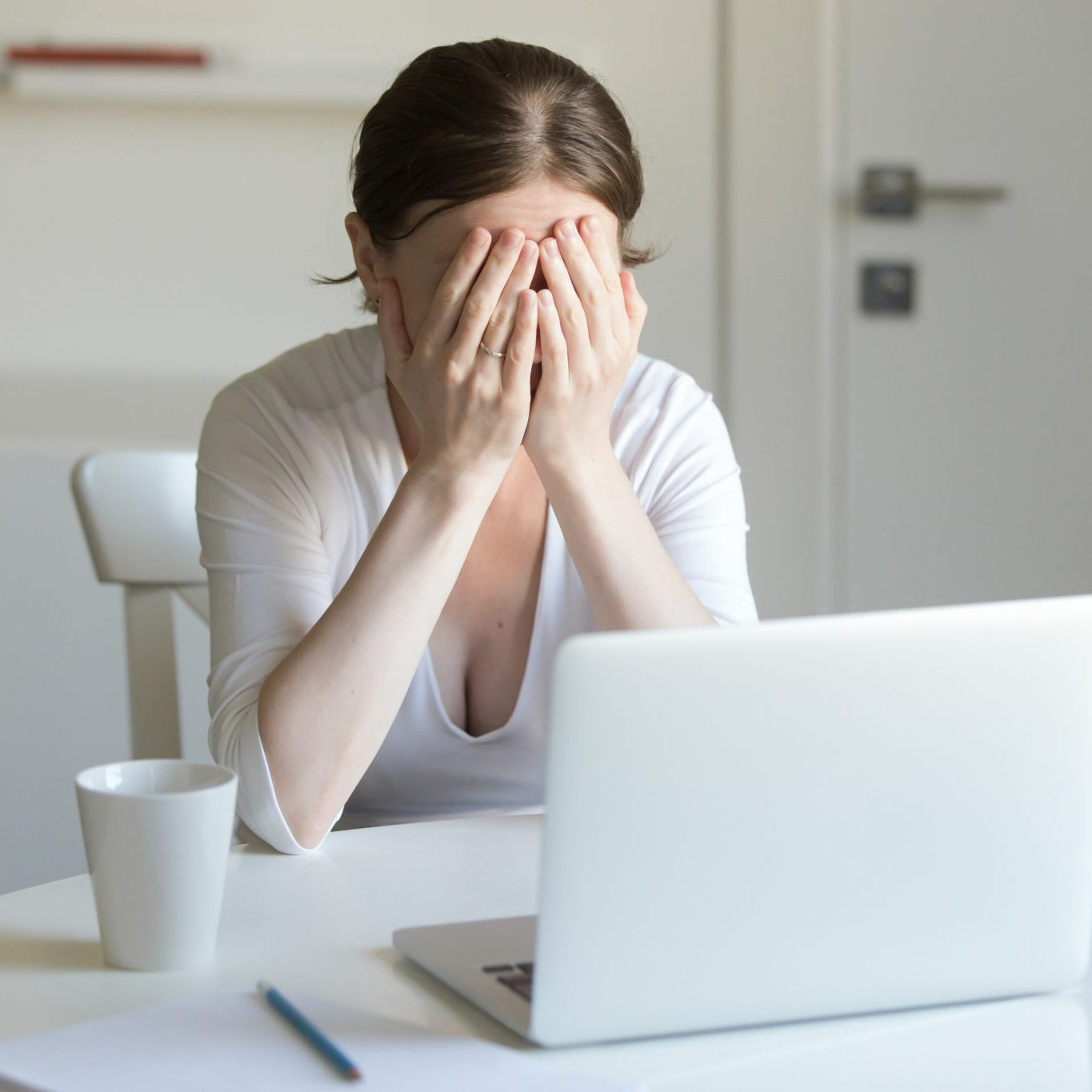 Portrait of a young woman at the desk with a laptop, her hands closing her face. Business concept photo, lifestyle